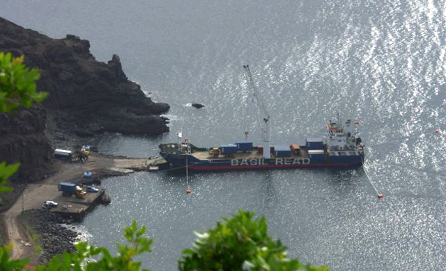 Picture taken from high ground, showing ship from above, with bow and stern ropes splayed out in all directions.