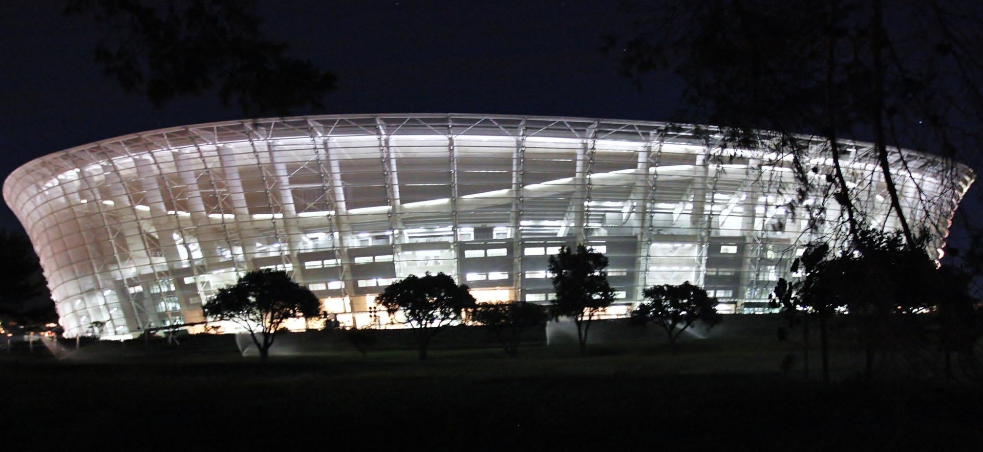 Night time view of the Cape Town Stadium, a framework of white light against a dark sky