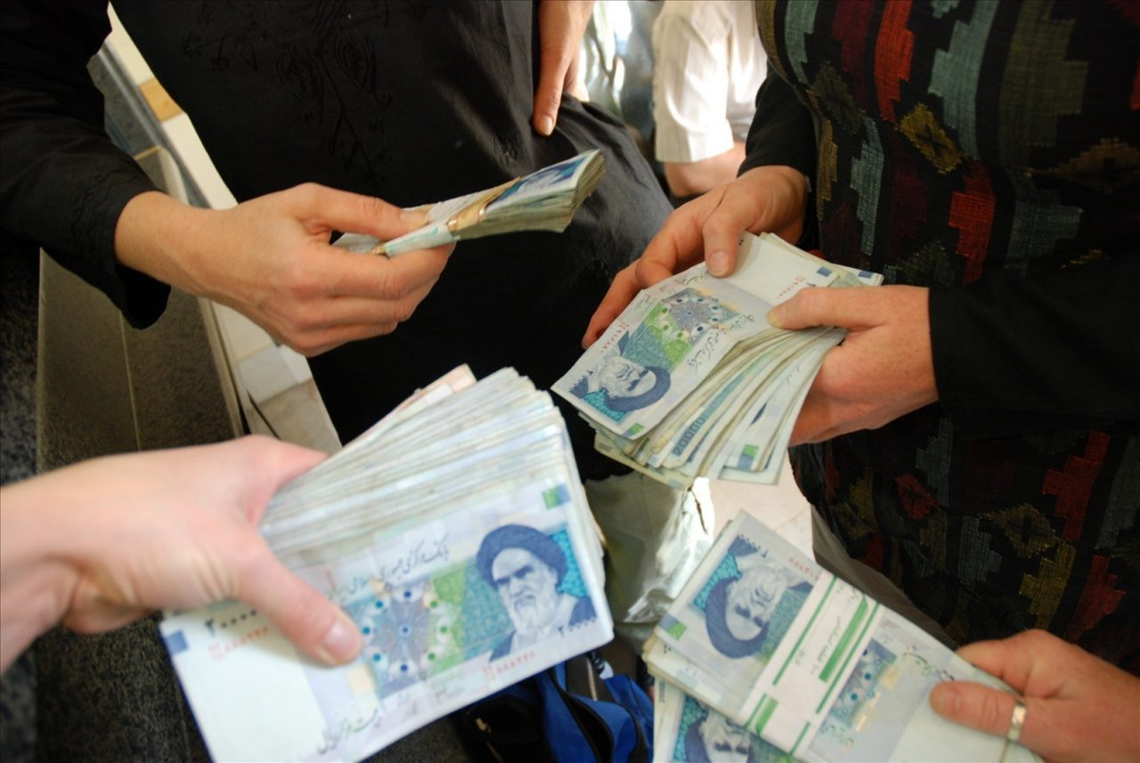 Close-up of hands holding bundles of blue Iranian Rial notes