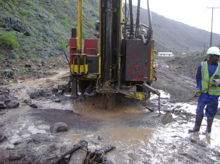 Wet mud around a drilling machine at the head of a valley on St Helena
