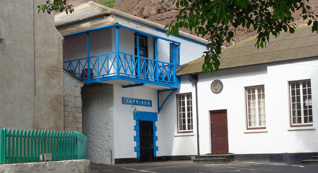 Entrance to HMP Jamestown, stone building with blue-painted wooden balcony above barred door