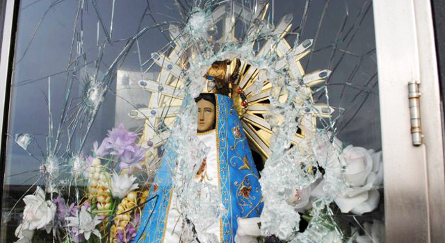the face of the Virgin Mary looks out from shattered glass