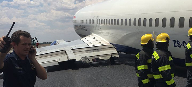 Fire crews stood by after a Comair plane collapsed after landing. Click the image to see Warren Mann's picture in full.